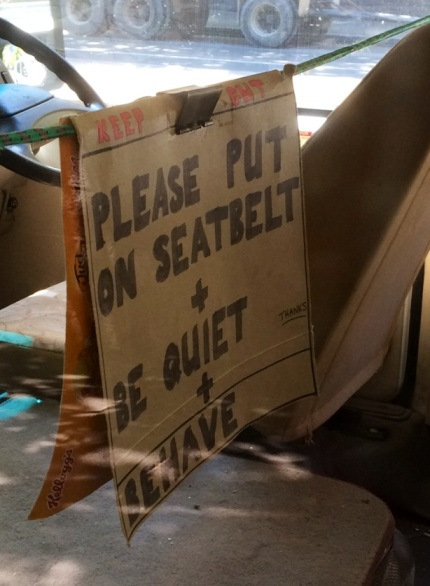 Sign in a school bus reads: 'Keep Out. Please put on seatbelt + be quiet + behave. Thanks'